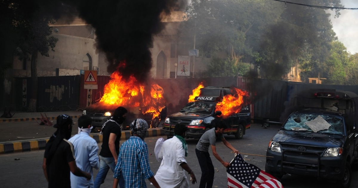 Pakistani Muslim demonstrators prepare to torch a US flag near burning police vehicles during a protest against an anti-Islam film in Karachi on September 21, 2012. At least 19 people died in Pakistan during violent protests on Friday condemning a US-made film insulting Islam, officials said.</p>