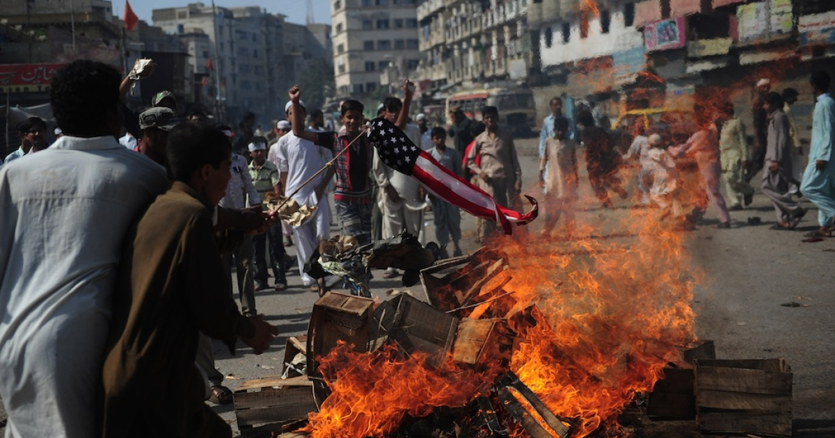 Pakistani Muslim demonstrators torch a US flag during a protest against an anti-Islam film in Karachi on September 21, 2012. At least 19 people died and nearly 200 were wounded in Pakistan during violent protests on Friday condemning a US-made film insulting Islam, defying a government call for only peaceful demonstrations, officials said.</p>