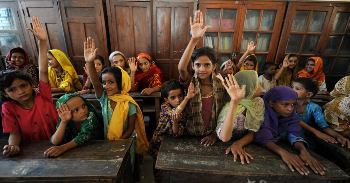 Pakistani children raise their hands.</p>