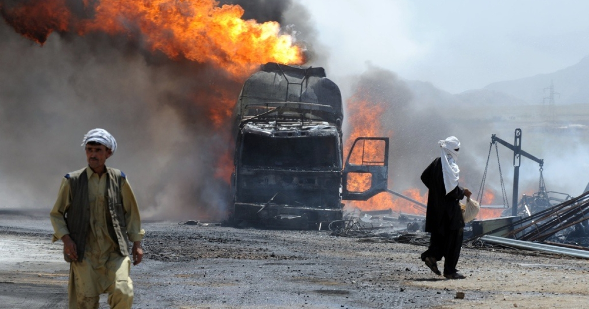 Local residents walk past a burning NATO supply truck after an attack by gunmen on the outskirts of Quetta on June 19, 2011.</p>