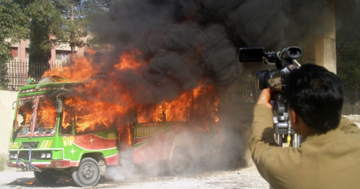 Pakistani media film a bullet-riddled burning bus in Quetta on October 4, 2011. Gunman attacked a bus carrying Shiite Muslims in Pakistan's insurgency-torn southwestern province of Baluchistan on October 4, killing 13 people and injuring six others, police said.</p>