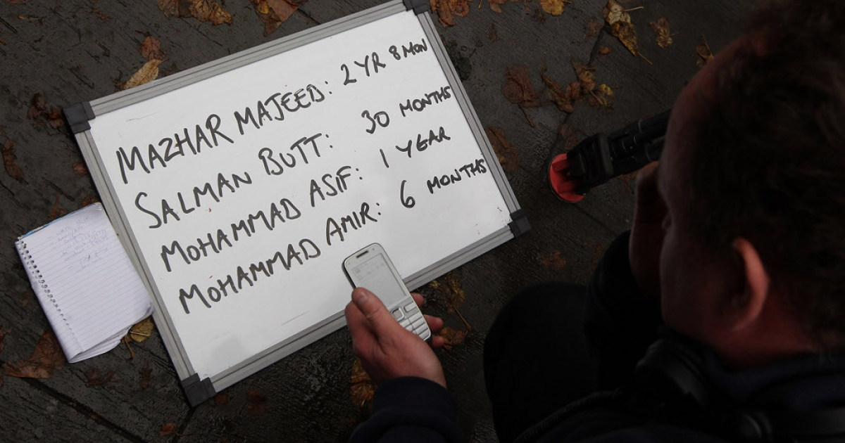 LONDON, ENGLAND - NOVEMBER 03: A television news producer writes the sentences received by Pakistan cricketers and their agent down on a board outside Southwark Crown Court on November 3, 2011 in London, England.</p>