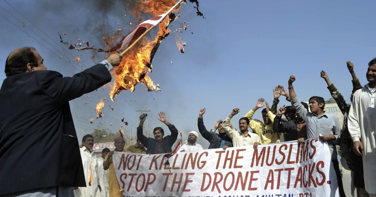 A Pakistani protester holds a burning US flag as they shout slogans during a protest in Multan on February 9, 2012 against the US drone attacks in the Pakistani tribal region.</p>