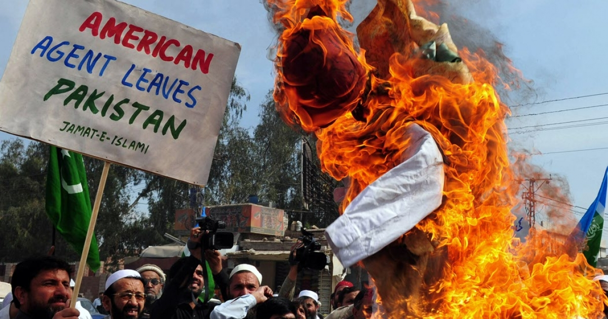 Activists of the Pakistani fundamentalist Islamic party Jamaat-i-Islami (JI) shout slogans beside a burning effigy of CIA contractor Raymond Davis during a protest in Peshawar on March 18, 2011. Thousands of people took to the streets across Pakistan on March 18 to protest a US drone strike that killed 35 people.</p>