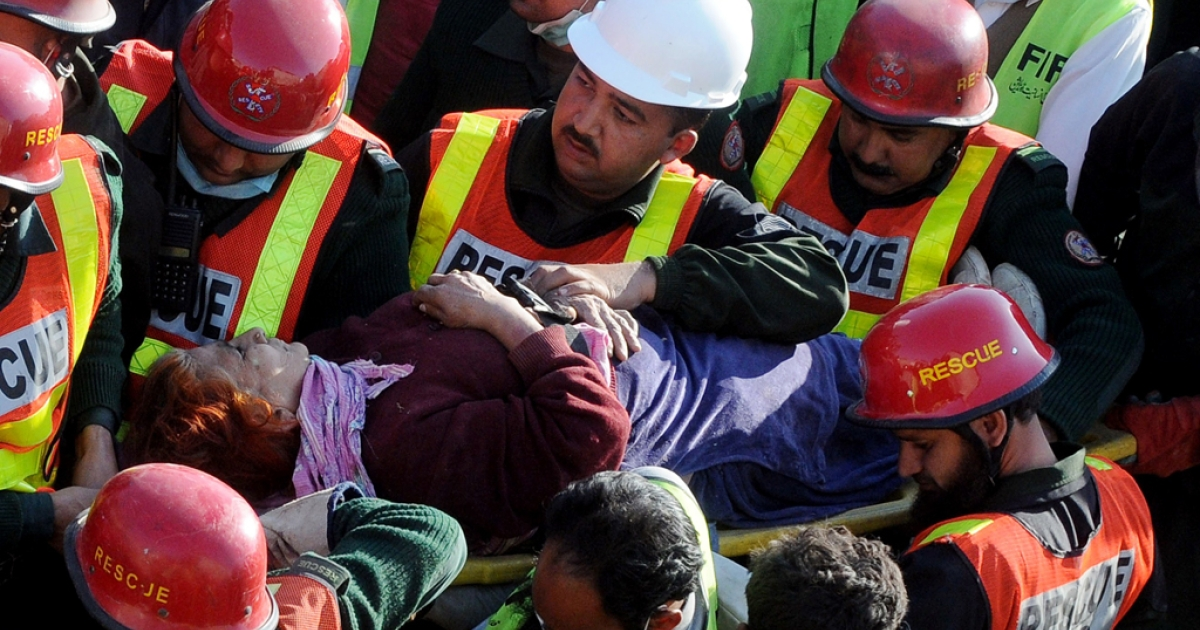 Pakistani rescue workers carry an elderly survivor on a stretcher during continued search for victims from the debris of a collapsed building in Lahore on February 7, 2012. Pakistani rescuers on February 7 plucked survivors from the rubble of a collapsed factory in Lahore, where another 10 people are still buried under the debris and the death toll rose to 19. The three-storey building used to manufacture veterinary medicines caved in from a probable boiler and a gas cylinder explosion at the premises in the congested Multan Road area of Pakistan's second largest city on February 6. AFP PHOTO / ARIF ALI</p>