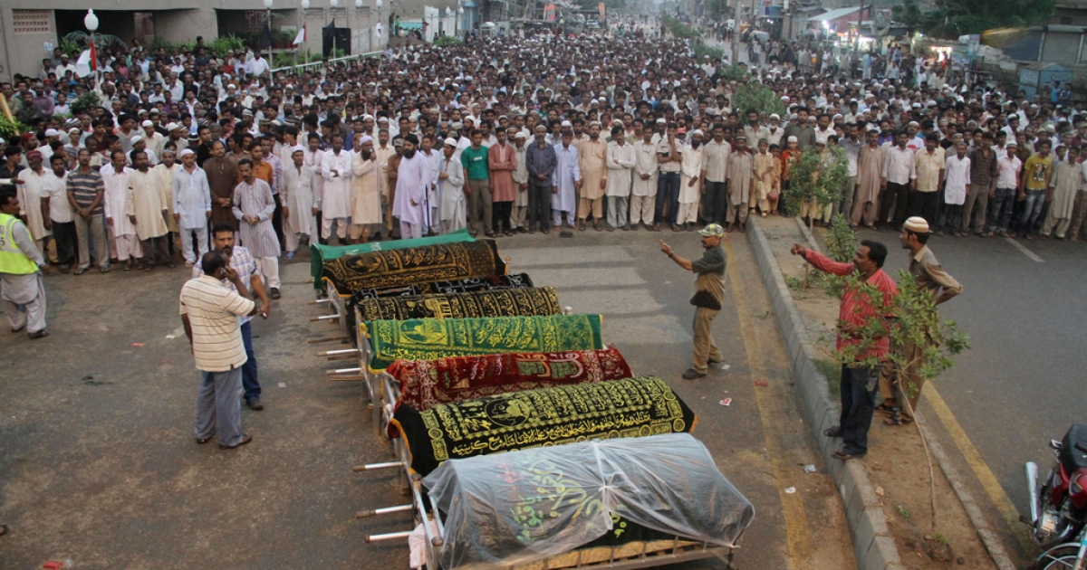 Pakistani Muslims offer funeral prayers of garment factory workers who were killed after fire erupted the factory in Karachi on September 12, 2012. Pakistani police registered murder cases against the factory owners and managers on September 13, 2012.</p>