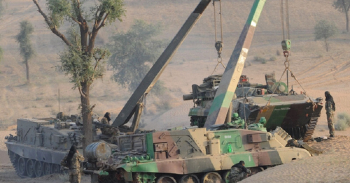 An Indian Army armoured personnel carrier (R) is lifted by cranes before maneuvers during the Shoor Veer military exercise near Hanumangarh, located near the India-Pakistan border, on May 3, 2012. More than 300 combat vehicles and 60,000 troops took part in the exercise held in the Indian desert state which borders Pakistan.</p>