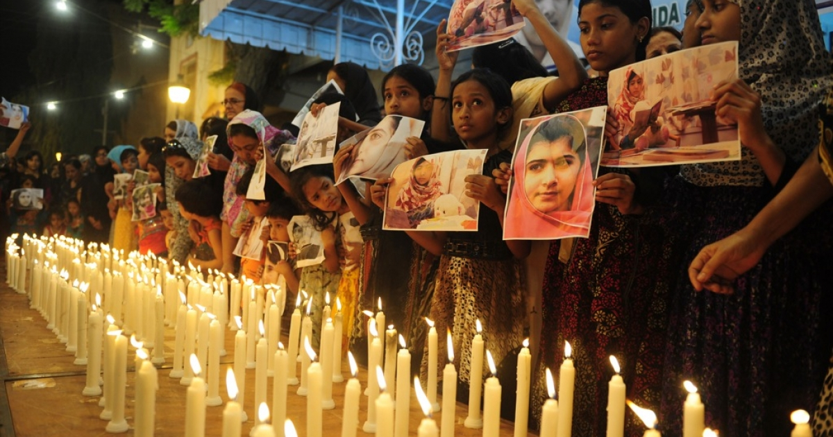 Pakistani supporters of the Muttahida Quami Movement (MQM) hold photographs of Pakistan's child activist Malala Yousafzai as they stand alongside burning candles during a ceremony to mark 'Malala Day' in Karachi on November 10, 2012.</p>