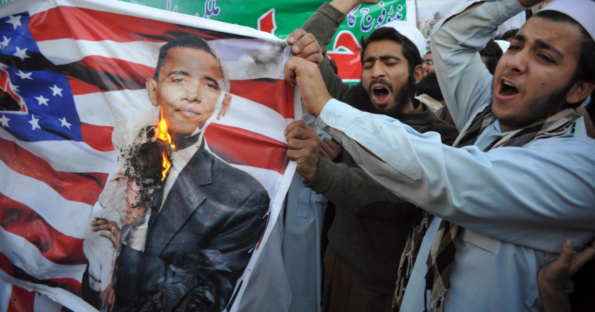 Pakistani protestors burn a portrait of President Barack Obama and a US flag during a demonstration in Peshawar on November 29, 2011, held to protest a NATO strike on Pakistan troops.</p>