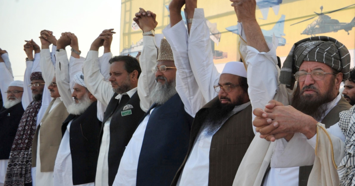Hafiz Saeed (second right), the head of banned charity Jamaat-ud-Dawa gestures as he sits with Maulana Sami ul-Haq (right) and others leaders of the Defense of Pakistan coalition raise hands in solidarity during a rally against the reopening of NATO supply to Afghanistan in Peshawar on April 15, 2012. Pakistan's insistence that no arms transit through its territory to Afghanistan is largely a gesture to quell domestic anti-US sentiment and will not hinder the resumption of NATO convoys, analysts say. Islamabad stopped NATO supplies travelling overland from its southern Karachi port to Afghanistan in November amid public outrage after 24 Pakistani soldiers were killed in a US air strike on a border post.</p>