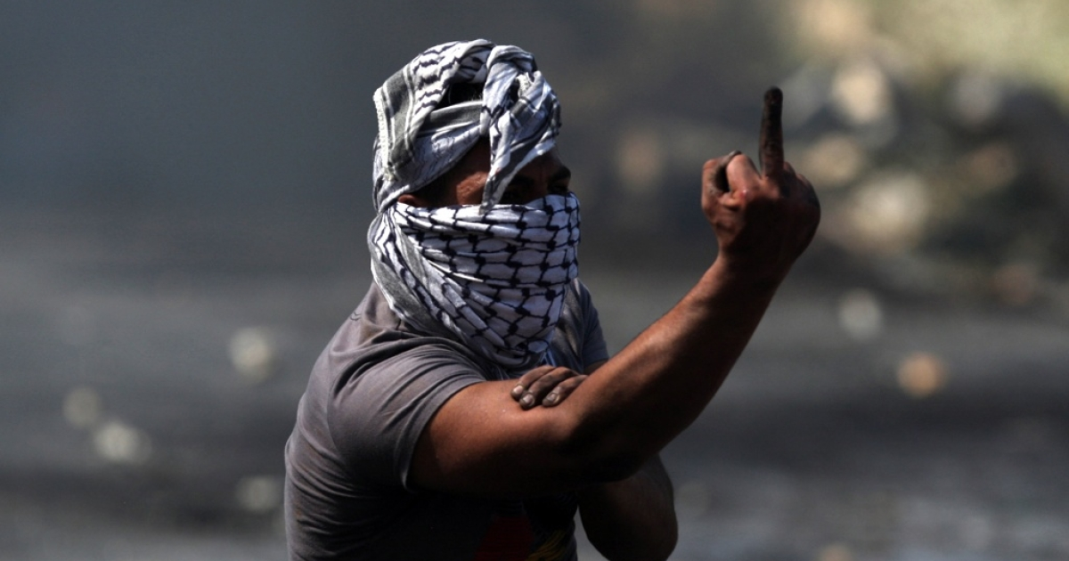A Palestinian protester gestures at Israeli soldiers near the West Bank city of Ramallah on May 15, 2012, marking Nakba day, which commemorates the exodus of hundreds of thousands of their kin after the establishment of Israel state in 1948.</p>