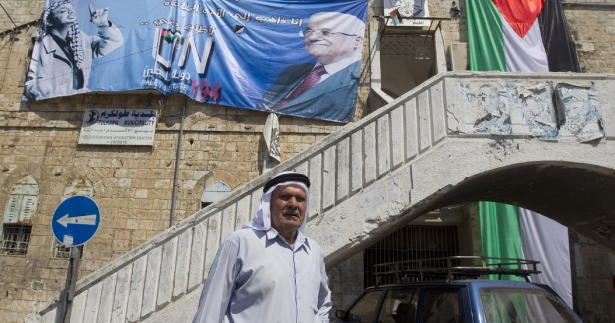 Palestinian municipal employees put in place a huge banner in support of the Palestinian UN bid for statehood at the United Nations on the facade of the former city hall in the northern West Bank city of Tulkarem.</p>