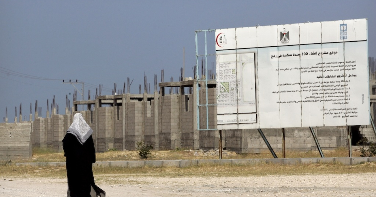 A Palestinian woman walks near an incomplete UN housing project in Rafah, Gaza Strip. Construction in Gaza has ground to a halt due to the Israeli blockade, preventing much needed construction materials from entering and creating widespread poverty and unemployment. Palestine faces economic calamity, according to a new report from a UN agency.</p>