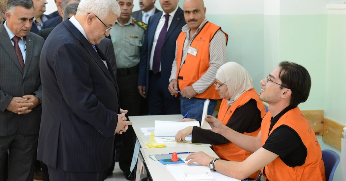 In this handout photo provided by the Palestinian Press Office (PPO), Palestinian President Mahmoud Abbas (L) votes in the municipal elections October 20, 2012 in Ramallah, West Bank. In their first chance to cast ballots in six years, Palestinians voted for mayors and local councils in 93 communities across the West Bank.</p>