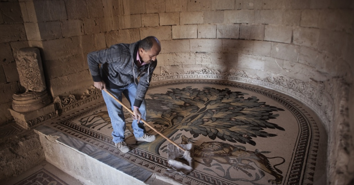 A Palestinian worker cleans the Tree of Life mosaic inside one of the rooms at the ancient Hisham Palace in the West Bank city of Jericho on December 2, 2010.</p>