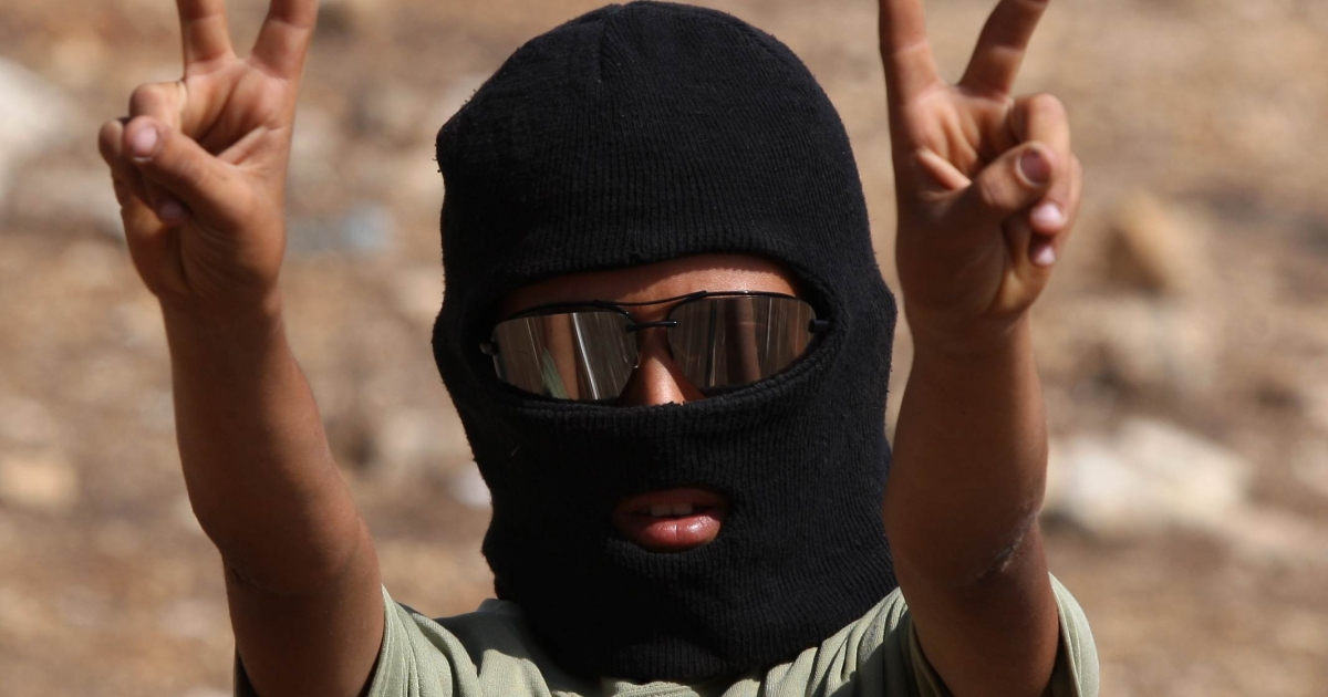 A masked Palestinian youth flashes the 'V' for victory sign during clashes with Israeli forces following a weekly demonstration against Israeli settlement expansion, in the West Bank village of Nabi Saleh, on October 7, 2011. ABBAS MOMANI/AFP/Getty Images</p>