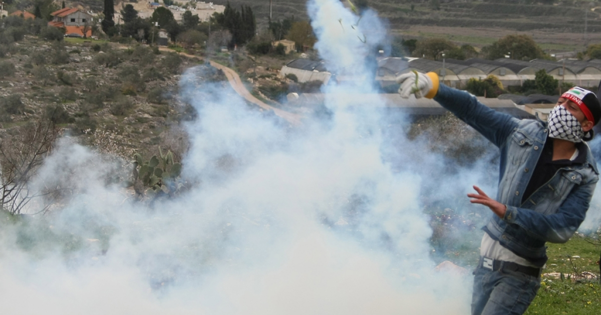 A Palestinian protester throws a tear gas canister back at Israeli soldiers during a demonstration against the expropriation of Palestinian land by Israel in the village of Kfar Kadum near the West Bank city of Nablus on January 13, 2012.    AFP PHOTO/JAAFAR ASHTIYEH</p>