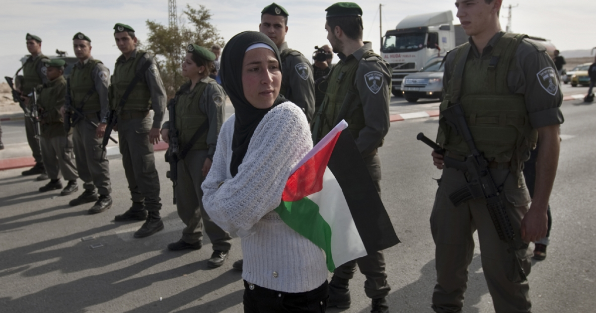A Palestinian woman holds a national flag as she stands in front of a line of Israeli soldiers blocking the main road leading to the West Bank city of Jericho on January 10, 2012 as some 60 Palestinians tried to drive in a motorcade on Route 60, the main Jewish settler road in the West Bank, to protest against Israeli curbs on Palestinian movement in the West Bank.     AFP PHOTO/AHMAD GHARABLI</p>