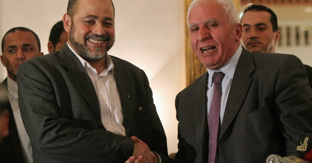Palestinian Fatah delegation chief Azzam al-Ahmed (R) shakes hands with Hamas deputy leader Mussa Abu Marzuq after a joint press conference in Cairo on April 27, 2011 as the rival Palestinian groups reached an 'understanding' to set up a transitional unity government and to hold elections, prompting a swift warning from Israel.</p>