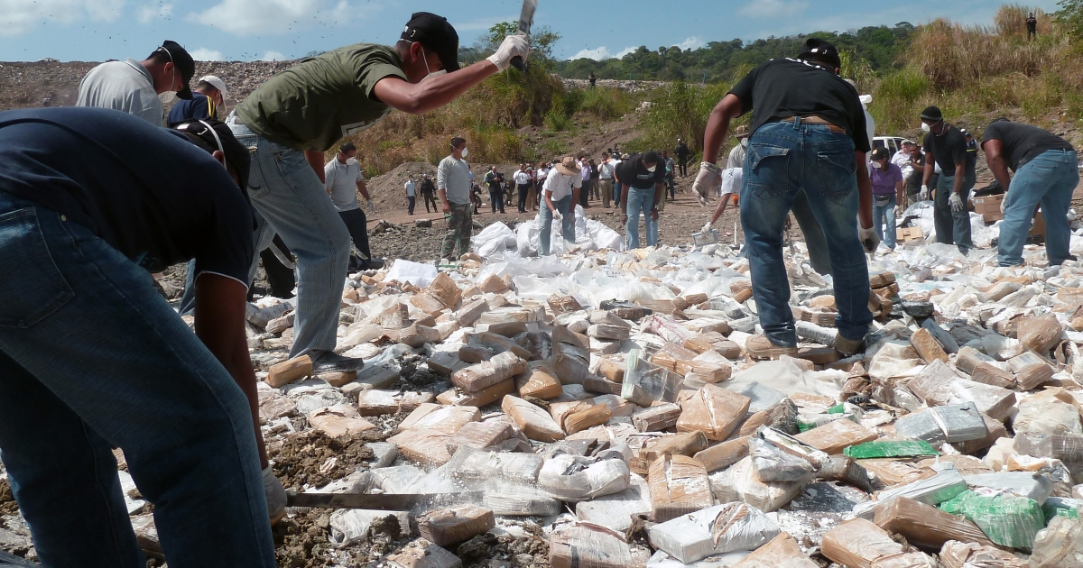 Panamanian policemen smash drug packages with machetes before being incinerated in Cerro Patacon, a dump in Panama City, on Jan.18, 2012. Panamanian authorities burnt 4.9 tons of drugs — 4.4 tons of cocaine, 0.4 tons of marihuana and 0.1 of other drugs.</p>