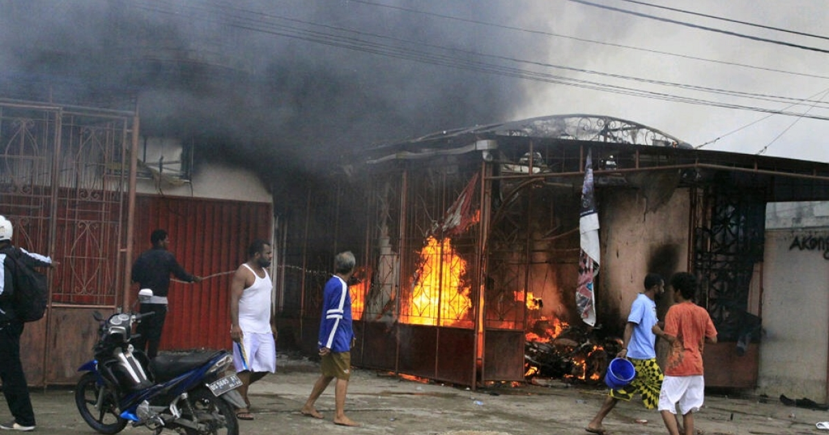 Residents try to extinguish a burning residence torched during riots in the town of Waena in Indonesia's Papua province, Waena on June 14, 2012.  There was also unrest in the provincial capital Jayapura.</p>