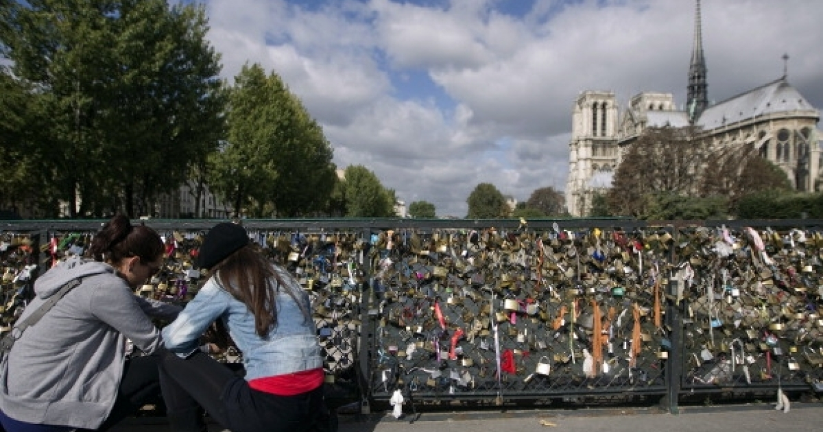 Two girls attach a padlock on a fence of the Pont de l'Archeveché bridge behind Notre-Dame (Our Lady) cathedral in Paris, on September 13, 2011. Lovers often throw the key into the river Seine as a sign of undying love, or keep it and open the padlock when they next return to the French capital.</p>