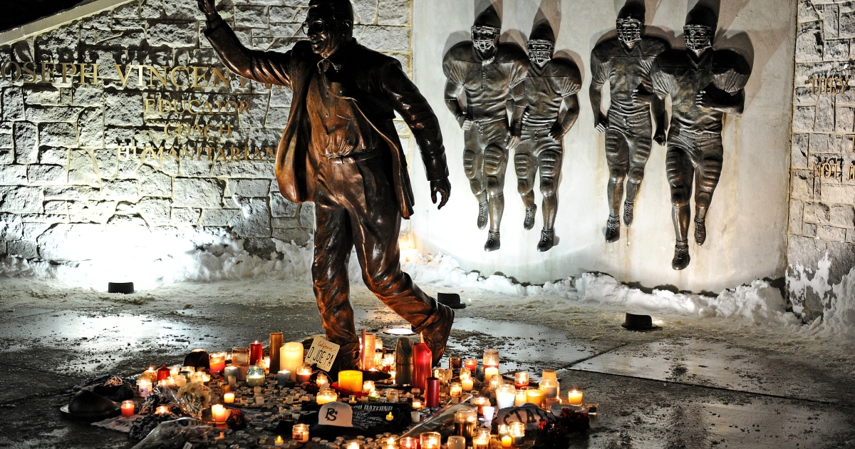 Candles, many burnt out, circle the statue of Joe Paterno, the former Penn State football coach, outside of Beaver Stadium in State College, Pa., in the early hours of Jan. 22, 2012.</p>