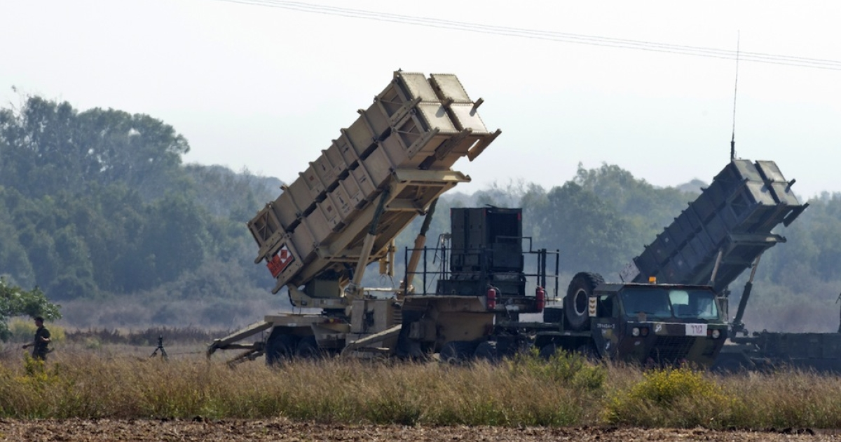 An Israli soldier walks nearby two patriot missile batteries, deployed on a field close to Atlit, on the outskirts of Haifa, on Oct. 22, 2012.</p>