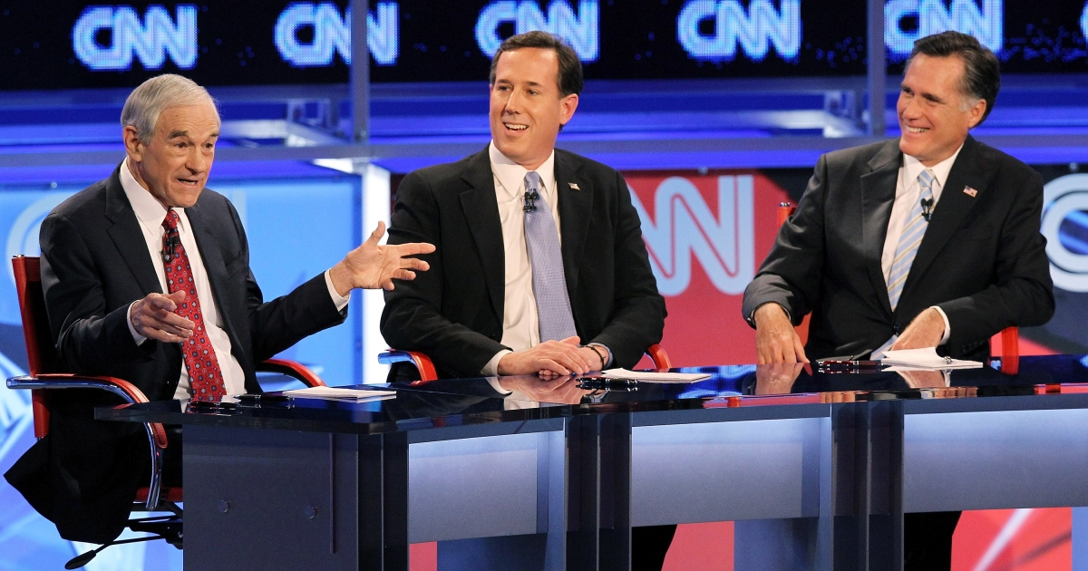 Rick Santorum, center, and Mitt Romney, right, watch as Ron Paul speaks at tonight's 20th Republican debate in Mesa, Ariz.</p>