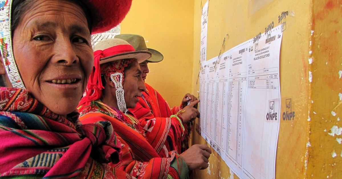 Andean indigenous women wearing traditional clothes look for their registration number at a polling station in the town of Aguas Calientes under the Inca ruins of Machu Picchu, during the presidential elections on June 5, 2011.</p>