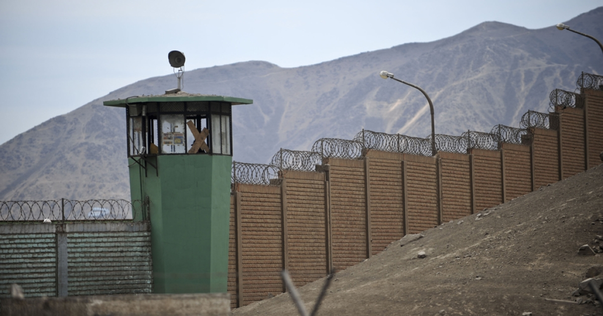 The fence and surveillance tower of the San Juan de Lurigancho prison in Lima, Peru's largest prison.</p>