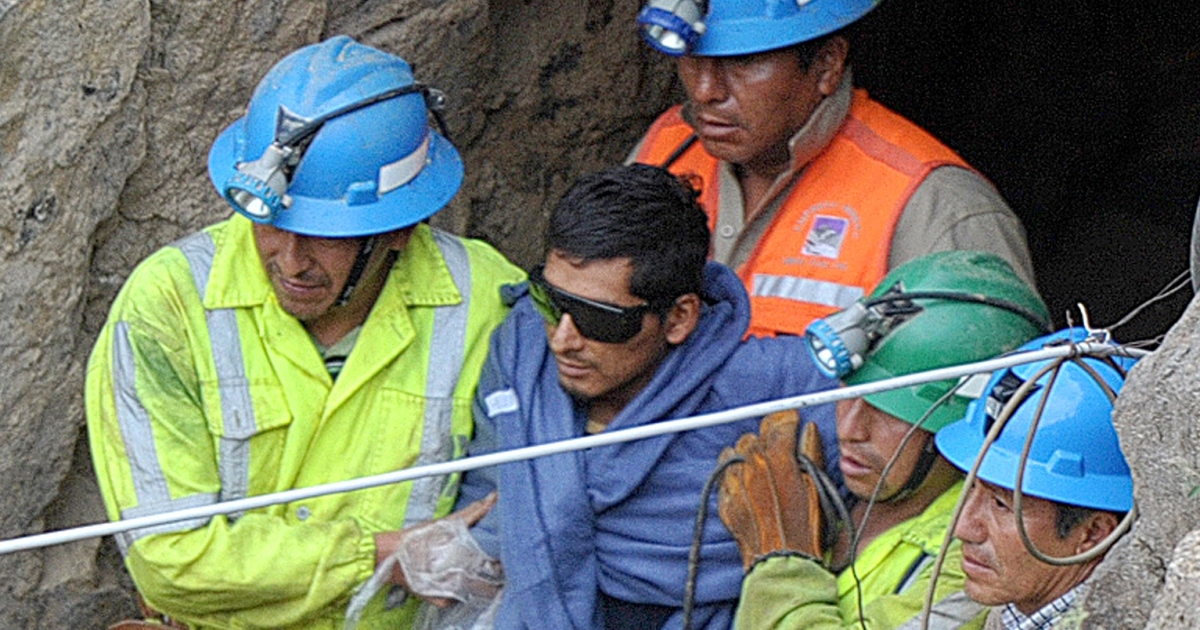 A rescued miner is ushered out of the Cabeza de Negro mine in southern Peru on April 11, after being trapped underground for six days.</p>