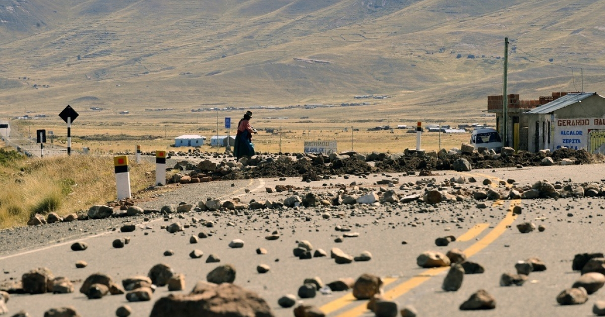 A Bolivian woman puts stones on the road linking Bolivia and Peru.</p>