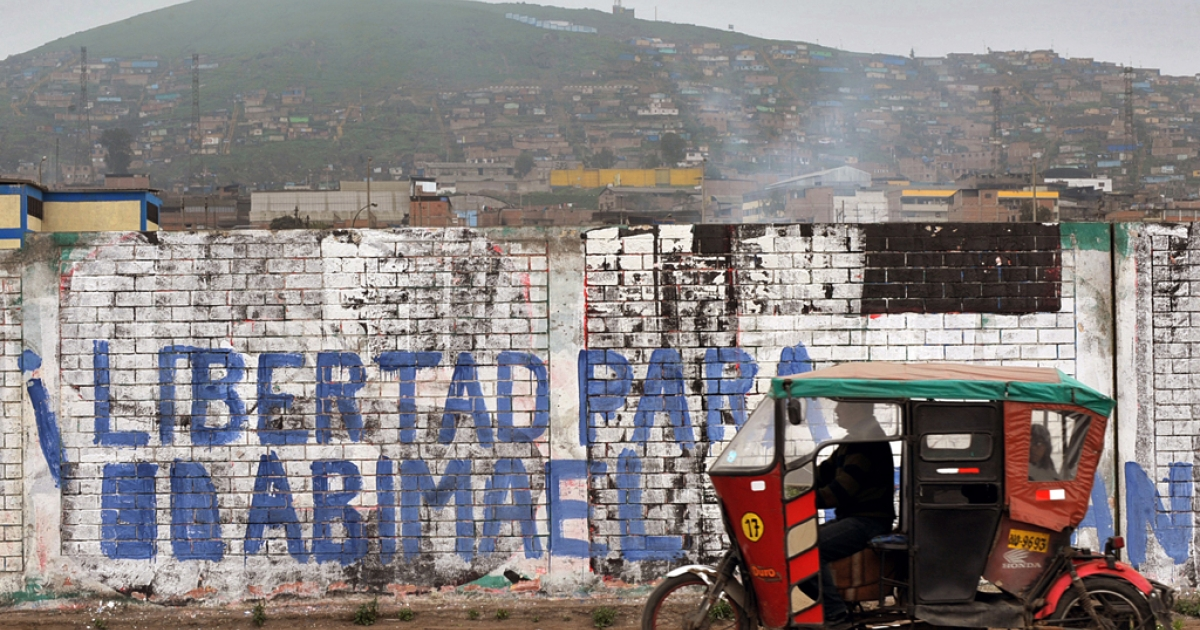 A rickshaw taxi drives past a graffiti reading