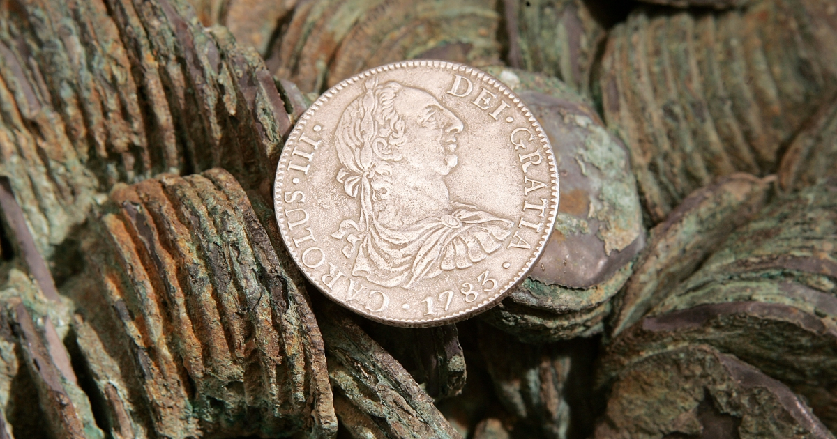 "An 8 Reales Silver coin dated 1783 is seen atop a cluster of those yet to be cleaned from The Franklin Mint's collection recovered from the sunken Spanish ship ""El Cazador.""</p>"