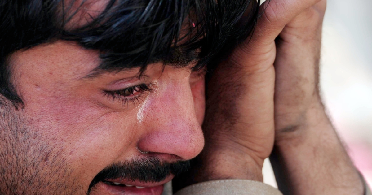 A Pakistani man mourns the death of his brother, one of 12 people killed in Thursday's attack on a bus station near Peshawar.</p>