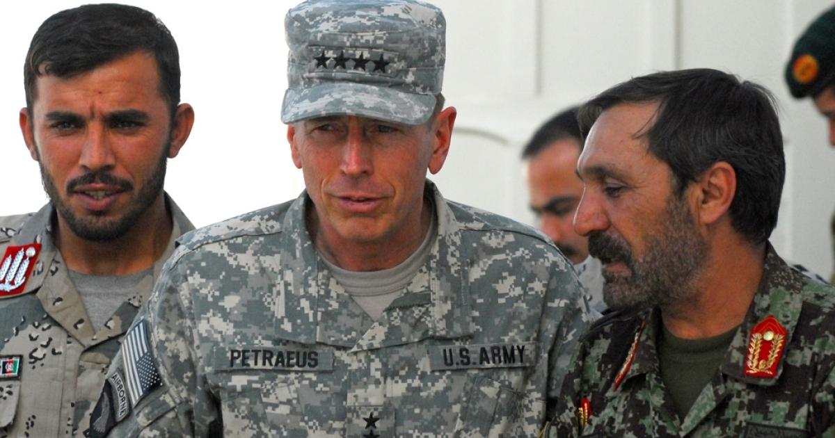 Gen. David Petraeus walks with Afghan National Security Forces in Kandahar, Afghanistan on April 7, 2011.</p>