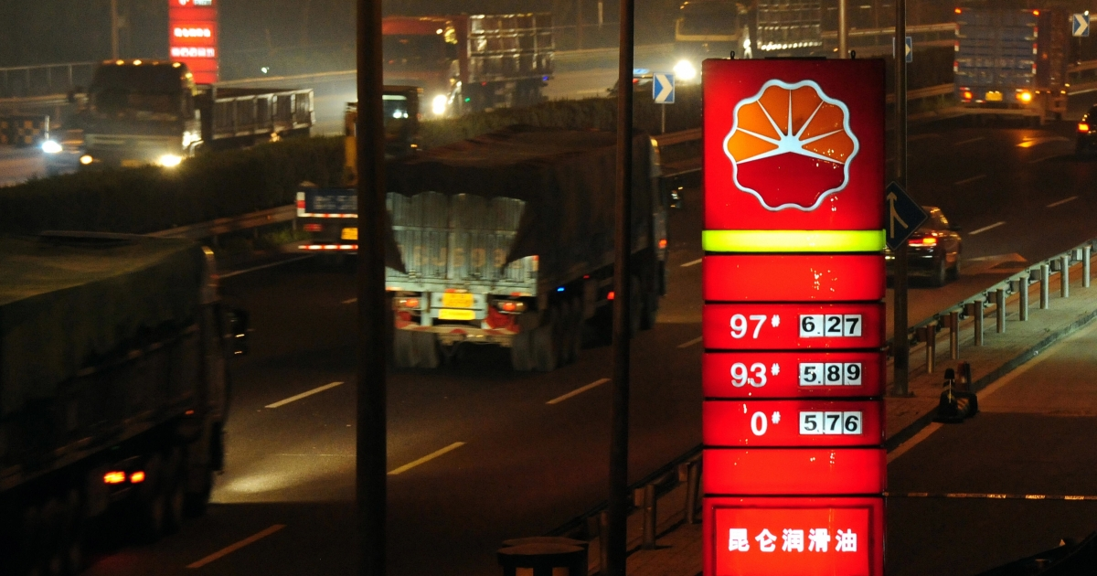 Delivery trucks on a late-night journey pass PetroChina gas stations in Beijing on June 28, 2009.</p>
