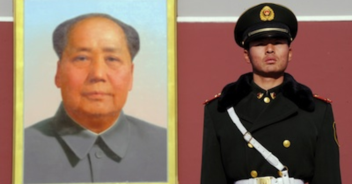 A Chinese paramilitary officer stands beneath a portrait of the late Chinese chairman Mao Zedong as military talks between China and the US open in Beijing on December 7, 2011.</p>