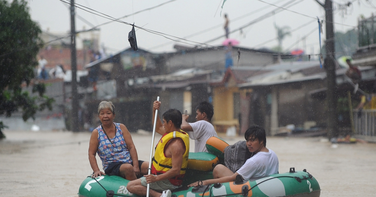 Residents evacuated from their flooded homes in the village of Tumana, Marikina town, in suburban Manila on Aug. 7, 2012, after torrential rains inundated most of the capital.</p>