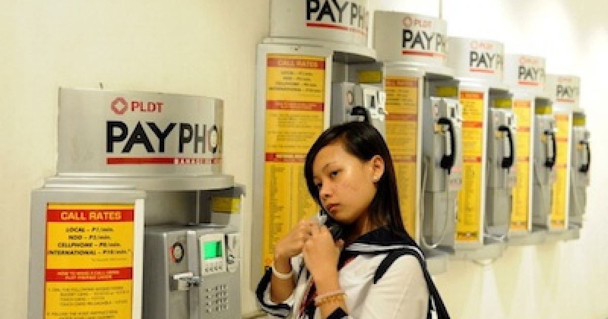A woman uses a Philippine Long Distance Telephone Co. (PLDT) phone in Manila on March 1, 2011.</p>