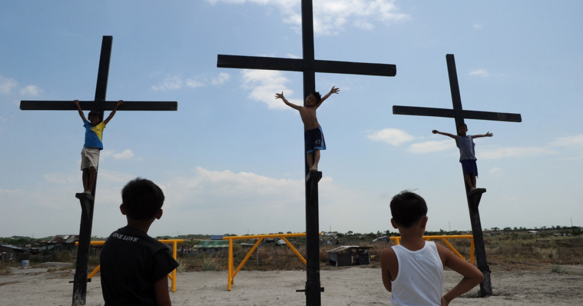Children play on wooden crosses as they mimic the crucifixion in the village of Cutud, in San Fernando, Pampanga province, north of Manila, on April 21, 2011, ahead of the traditional Good Friday Easter celebratations where penintents are nailed to the cross.</p>