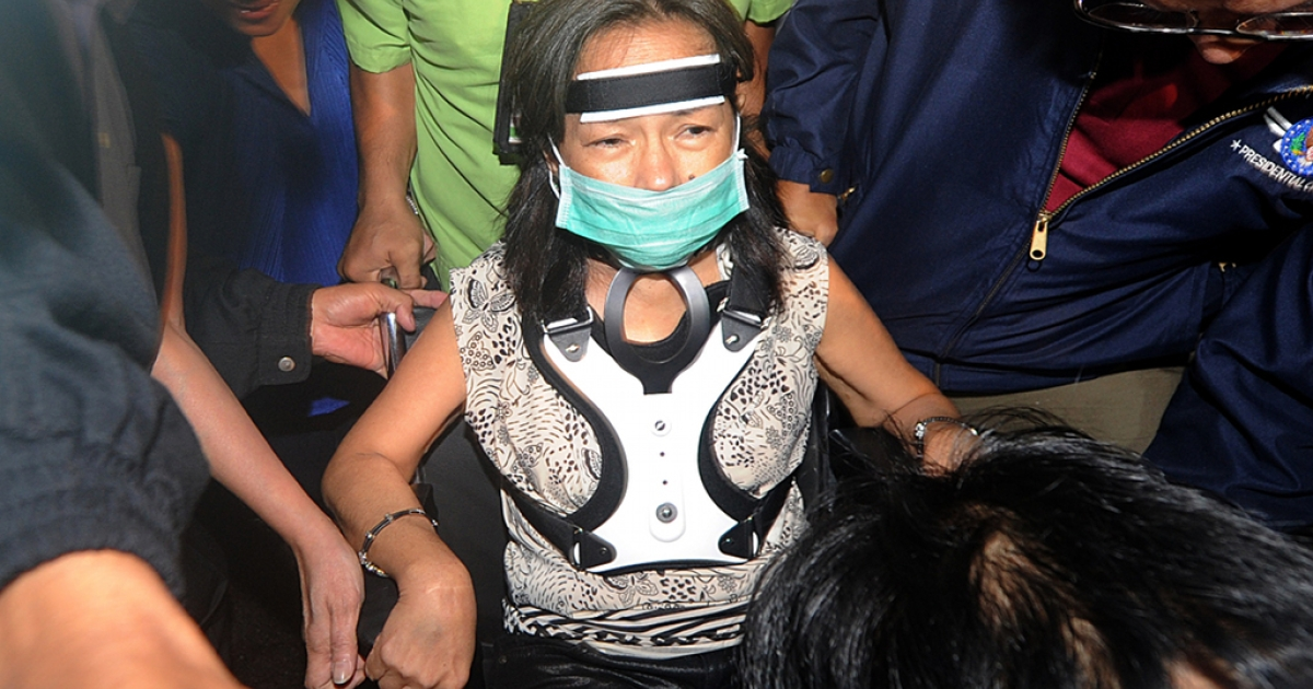 In a file picture taken on November 15, 2011, former Philippine President and congresswoman Gloria Arroyo (C) arrives at the Manila International Airport in Manila.</p>