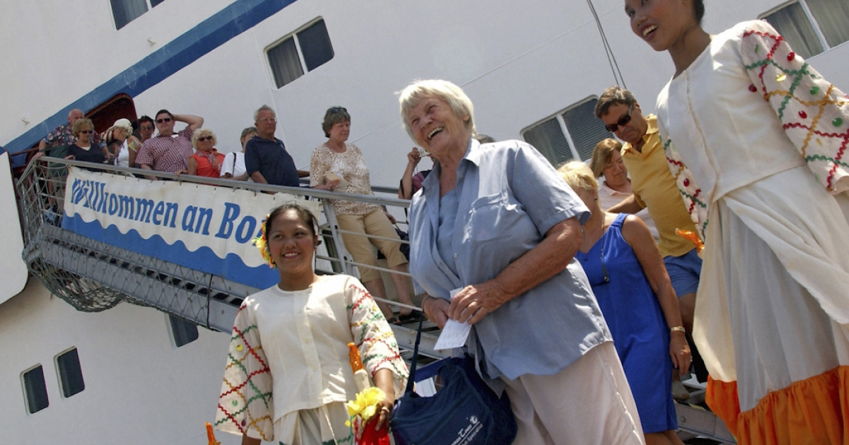 German tourists disembark from cruiseship M/V Astor shortly after arriving in Zamboanga city, southern Philippines, on March 5, 2007.</p>