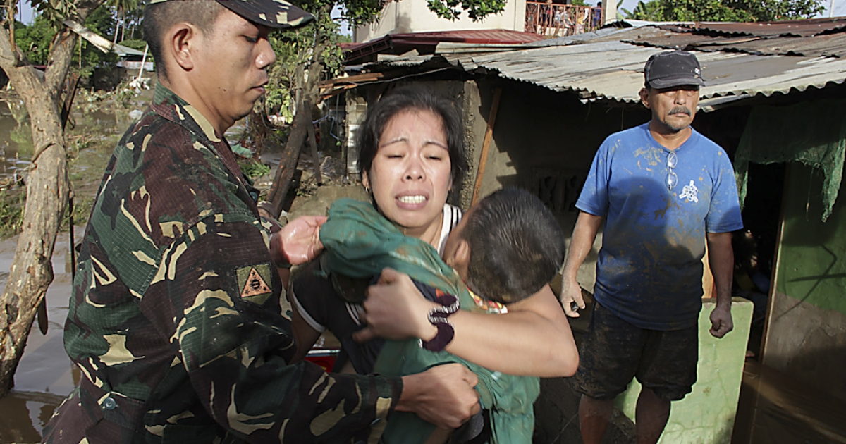 A soldier helps a woman holding the dead body of her child killed during the passage of Tropical Storm Washi at a village in Iligan City, on the Philippines island of Mindanao. More than 650 people were killed, and 800 more are still missing, after the storm triggered widespread flash floods in the southern Philippines.</p>