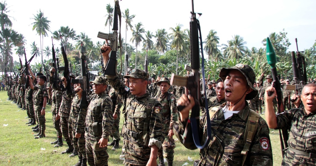 This photo taken on October 15, 2012 shows members of the Moro Islamic Liberation Front (MILF) rebels raising their rifles during a ceremony at Camp Darapanan in Sultan Kudarat, Maguindanao province on the southern Philippine island of Mindanao to coincide with the signing of an accord between the government and rebels' representatives in the Philippines capital city of Manila.</p>