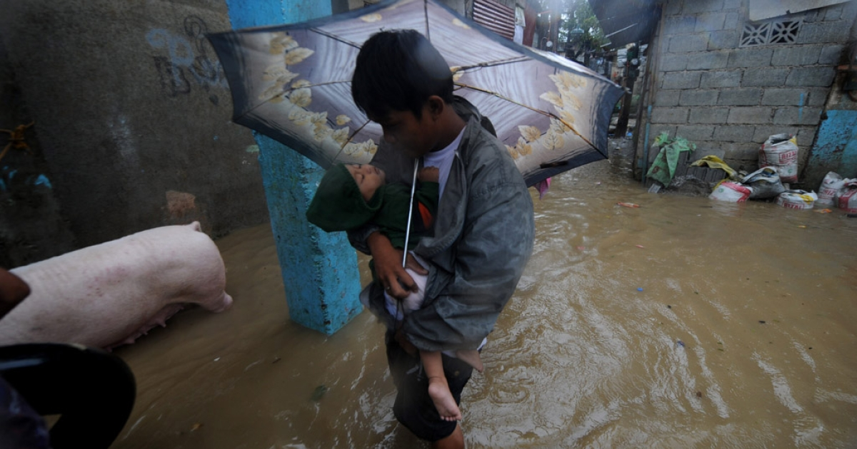 A man carries a child along a flooded street during typhoon Nesat east of Manila on September 27, 2011. Typhoon Washi has claimed over 700 lives in the southern part of the region so far, officials reported.</p>