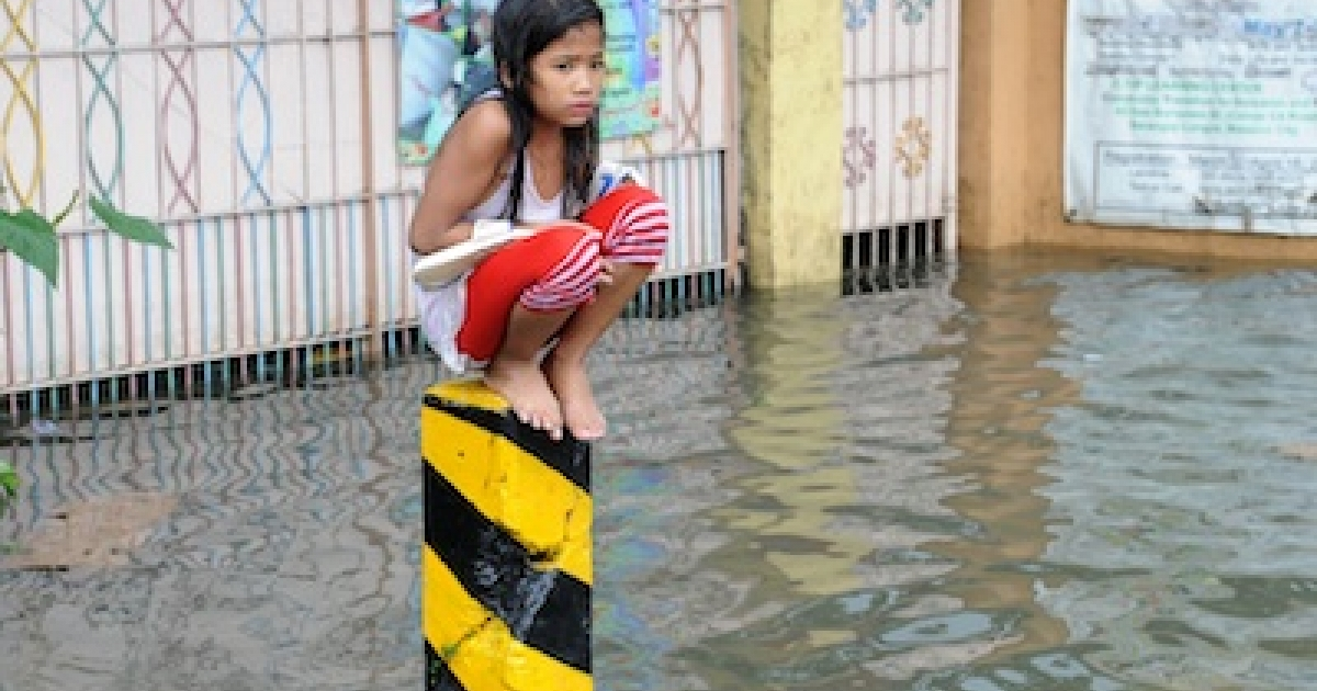 A soaking wet child sits on a post on a flooded street in suburban Manila on August 8, 2012. More than one million people in and around the Philippine capital battled deadly floods on August 8 amid relentless monsoon rains.</p>