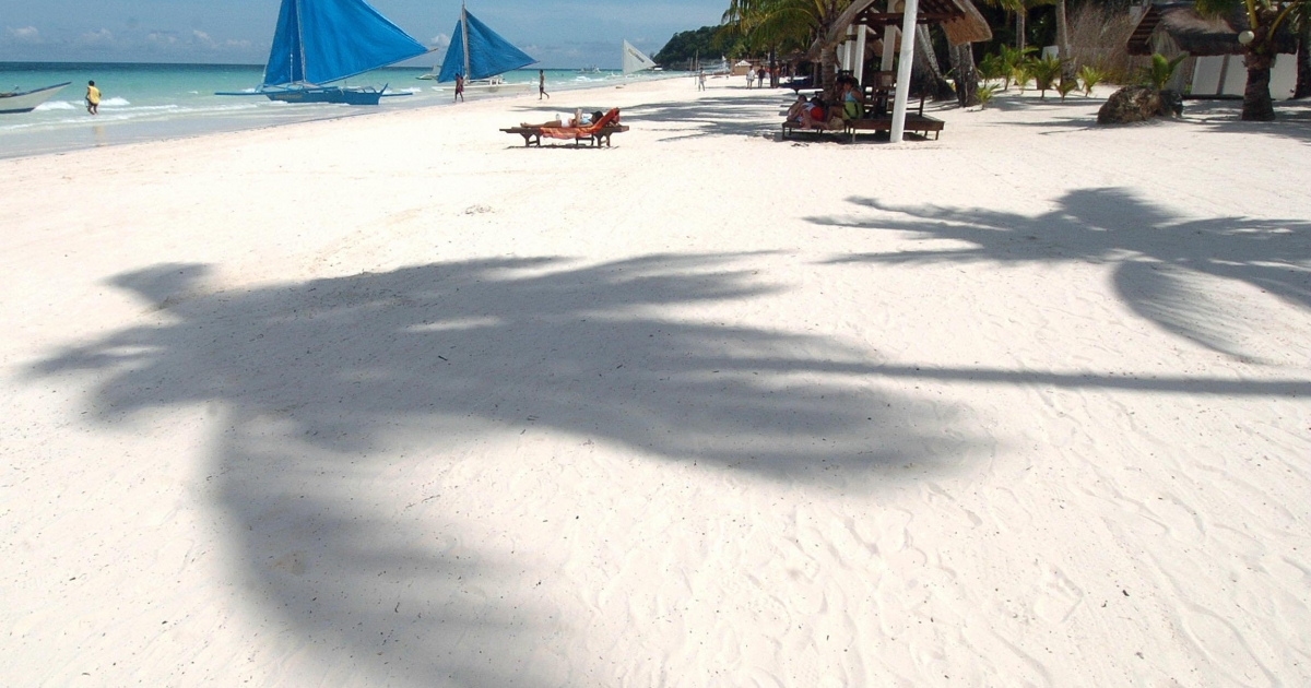 A tourist relaxes near the shadows of coconut trees on the fine, white sand of the central Philippine island of Boracay.</p>