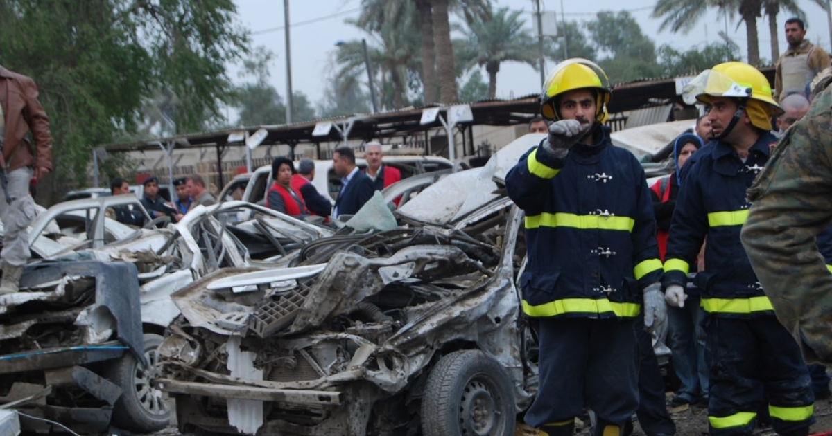Iraqi civil defense workers at the scene of a suicide car bombing outside the appeals court in the Mansour district of Baghdad.</p>